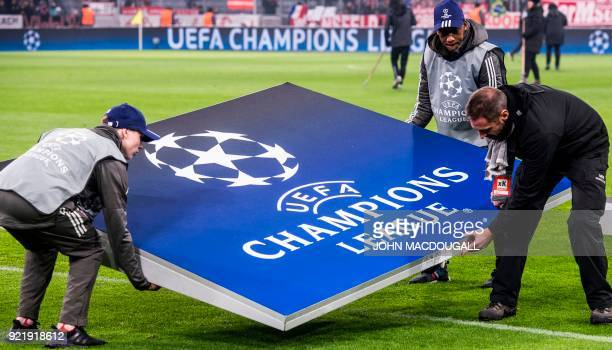 Workers carry a giant Champions League logo prior to the start of the UEFA Champions League round of sixteen first leg football match Bayern Munich...