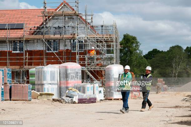 Workers carry a pane of glass on a construction site near Guildford southwest of London on May 11 2020 The British prime minister on May 10 announced...