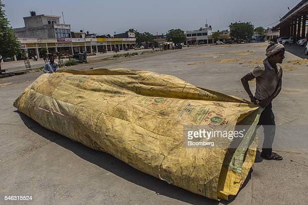 Workers carry a tarp at the New Grain Market in Karnal Haryana India on Thursday May 19 2016 India exported about 25 cubic kilometers of water...