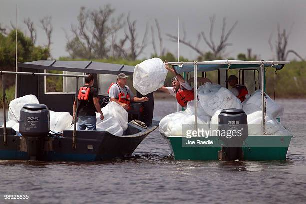 Workers carry absorption pads in their boats as they prepare to place them into the water in an effort to protect the coast line from the massive oil...
