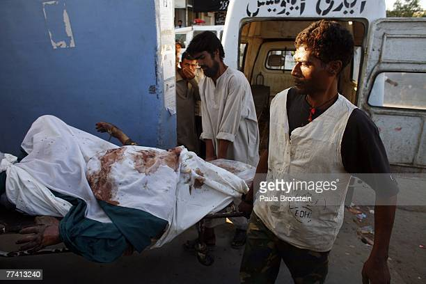 Workers carry another body into the Edhi Morgue October 19 2007 in Karachi Pakistan A suicide bombing killed at least 136 people in an assassination...