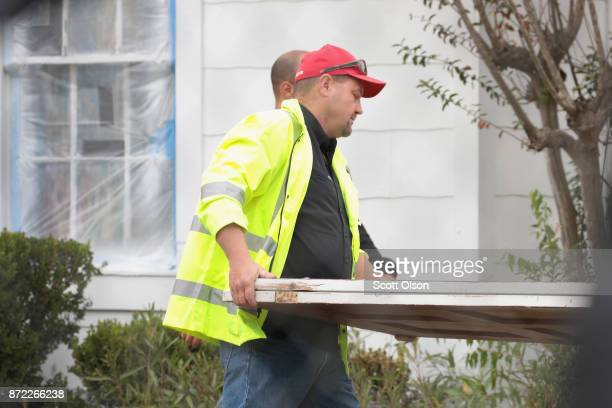 Workers carry away the bulletscarred front door of the First Baptist Church of Sutherland Springs on November 9 2017 in Sutherland Springs Texas The...