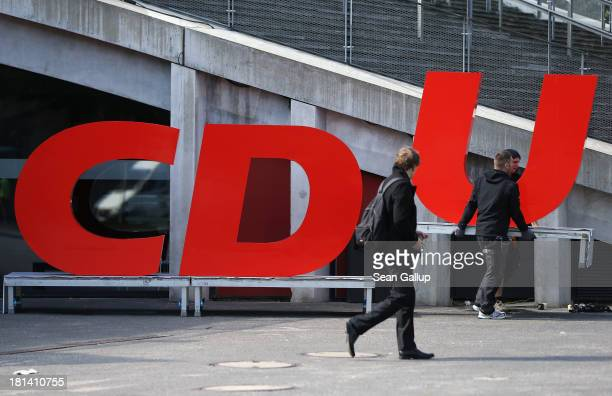Workers carry away the giant letters of the German Christian Democrats following a CDU election rally the day before federal elections on September...