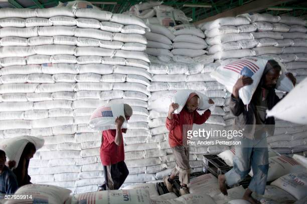 Workers carry bags of wheat donated by the US government to WFP to distribute in Ethiopia on November 9 2010 in central Nazareth Ethiopia Many trucks...