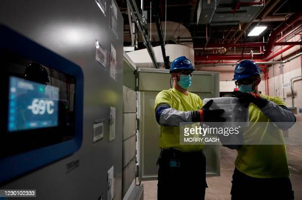 Workers carry boxes containing the Pfizer-BioNTech Covid-19 vaccine as they are prepared to be shipped at the Pfizer Global Supply Kalamazoo...