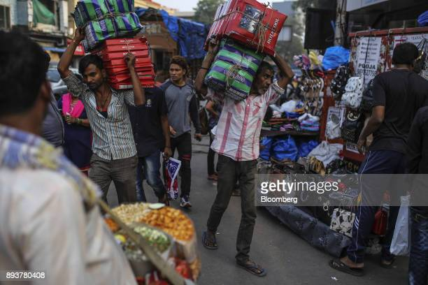 Workers carry boxes past roadside stalls in Mumbai India on Friday Dec 15 2017 India's inflation surged past the central bank's target bolstering a...