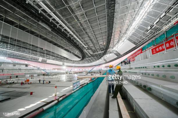 Workers carry building material inside the underconstruction National Speed Skating Oval the venue for speed skating events at the Beijing 2022...