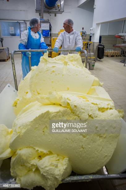Workers carry churn butter in a manufacture in Echire western France on March 17 2015 The unique process in France is used for a hundred years in the...