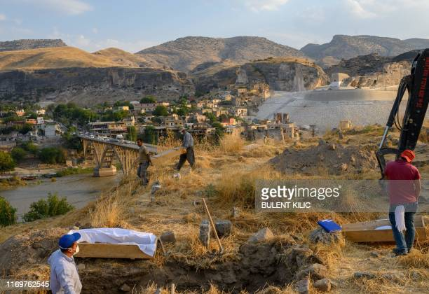 Workers carry coffins as they move the corpses from the old Hasankeyf cemetery to the new cemetery on the banks of the Tigris in southeastern Turkey...