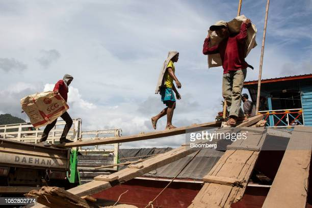 Workers carry construction materials from a barge at a dock near the Luang Prabang railway bridge a section of the ChinaLaos Railway built by the...