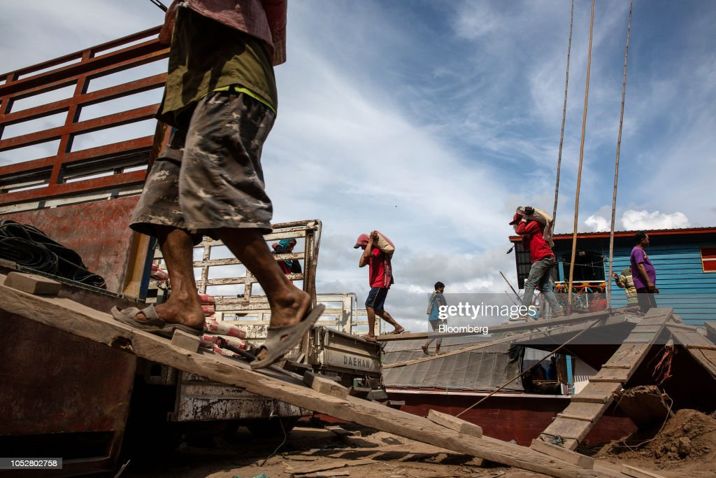 Workers carry construction materials from a barge to a dock