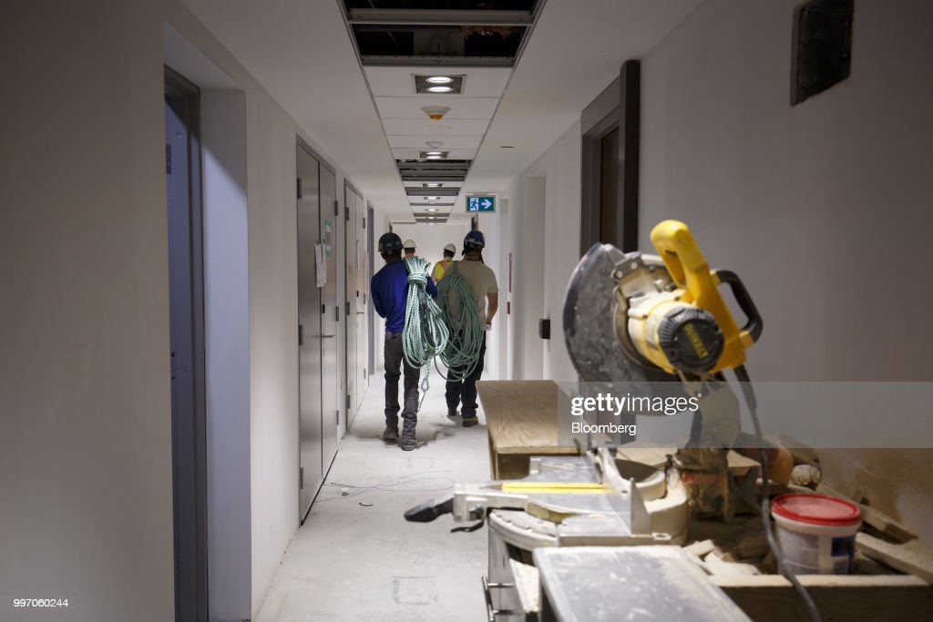 Workers carry equipment during construction of the GWL Realty Advisors Livmore luxury apartment building in Toronto, Ontario, Canada, on Tuesday, July 10, 2018. Toronto's rental market is going upscale to meet surging demand from millennials and downsizing baby boomers who want a little more than your average walkup while providing a steady income stream for institutions such as pension funds. Photographer: Cole Burston/Bloomberg via Getty Images