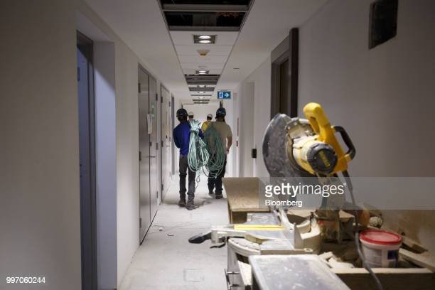 Workers carry equipment during construction of the GWL Realty Advisors Livmore luxury apartment building in Toronto Ontario Canada on Tuesday July 10...