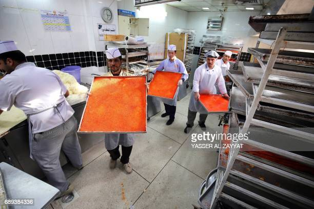 Workers carry large trays of Kunafa a popular Arabic sweet to be sold at a shop during the second day of the Holy fasting month of Ramadan in Kuwait...