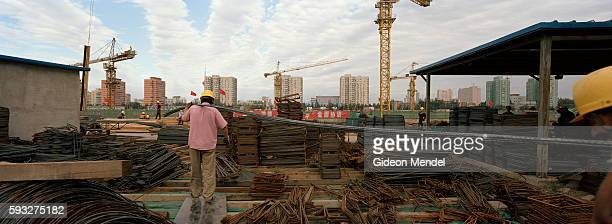 Workers carry long steel reinforcing rods while constructing the Wukesong Indoor Stadium for the 2008 Beijing Olympics The stadium will house...