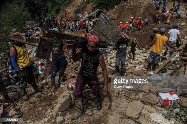 Workers carry metal debris as rescuers dig at the site where people were believed to have been buried by a landslide on September 18 2018 in in...