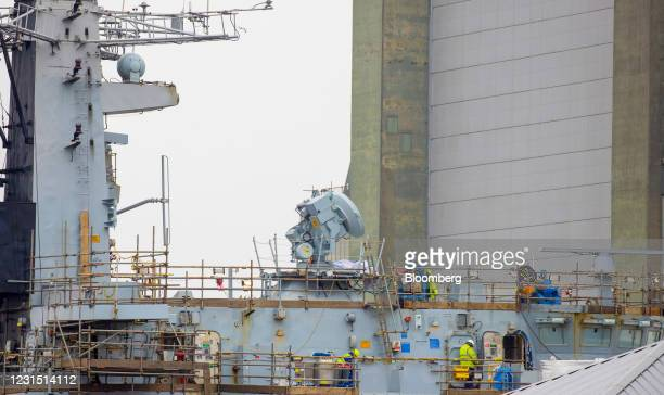 Workers carry out maintenance on a ship in a dock operated by Babcock International Group Plc near the site of the Devonport freeport in Plymouth,...