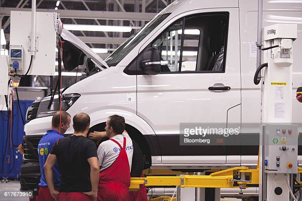 Workers carry out quality control inspections on a Volkswagen AG Crafter van on the final assembly line inside the newly opened Volkswagen AG...