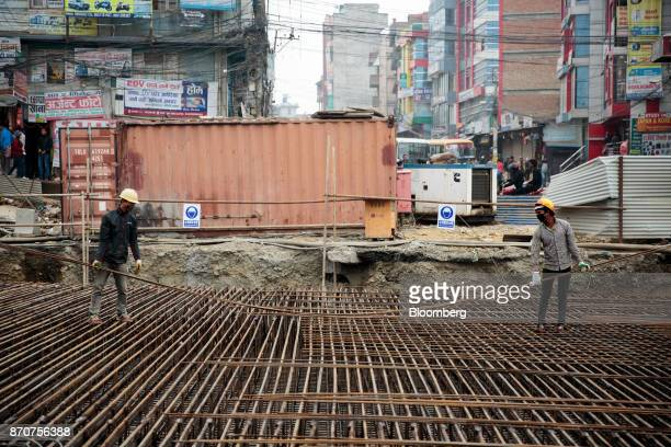 Workers carry reinforcing steel at a construction site for a road operated by Shanghai Construction Group Co in the Kalanki Chowk area of Kathmandu...
