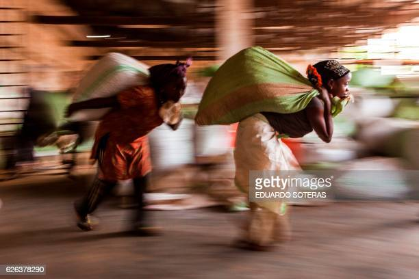 Workers carry sacks of cocoa beans at the SCAK cocoa processing plant in Beni on November 14 2016 Cocoa farming in the Beni area started in the late...