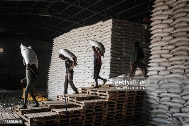 Workers carry sacks of wheat from stocks for a food distribution for 4503 people, who fled the violence in Ethiopia's Tigray region, organised by the...