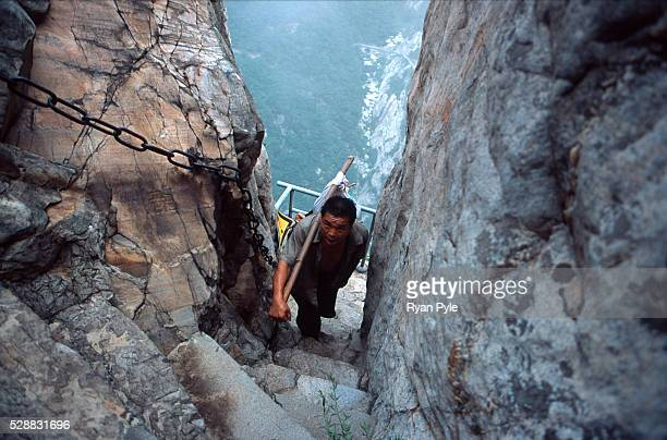 Workers carry supplies from the base to the summit temple of the Song Shan holy mountain in Songshan, Henan, China. Song Shan is a Taoist holy...