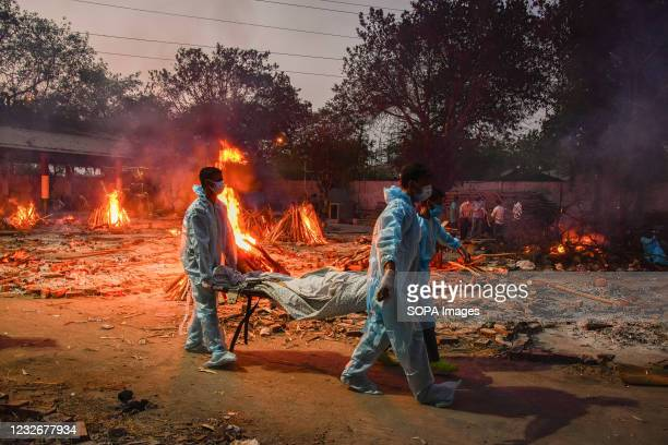 Workers carry the body of a person who has died of the Covid-19 coronavirus disease as other funeral pyres are seen burning during a mass cremation...