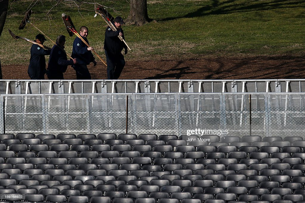 Workers carry tools as they walk among empty seats at the U.S. Capitol building as Washington prepares for U.S. President Barack Obama's second inauguration on January 20, 2013 in Washington, DC. Both Obama and U.S. Vice President Joe Biden will be officially sworn in today with a public ceremony for the President taking place on January 21.
