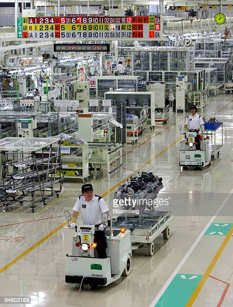 Workers carry V8 engines of Toyota Motor Corp's luxury series Lexus LS600 hybrid sedan on the production line at its Tahara plant in Tahara central...