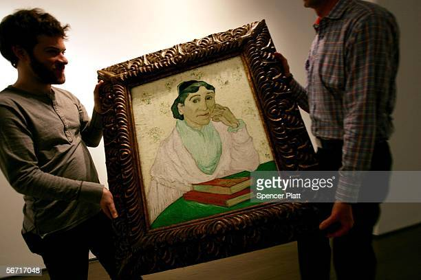 Workers carry Van Gogh's L'Arlesienne Madame Ginoux down a hall at Christie's auction house February 1 2006 in New York City The painting is expected...