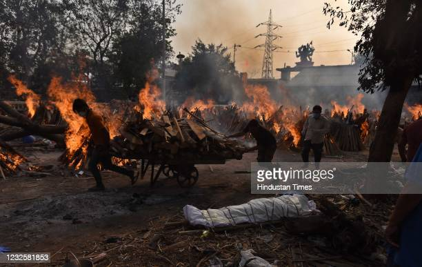 Workers carry wood amid burning funeral pyres of Covid-19 victims during a mass cremation, at Gazipur crematorium on April 28, 2021 in New Delhi,...