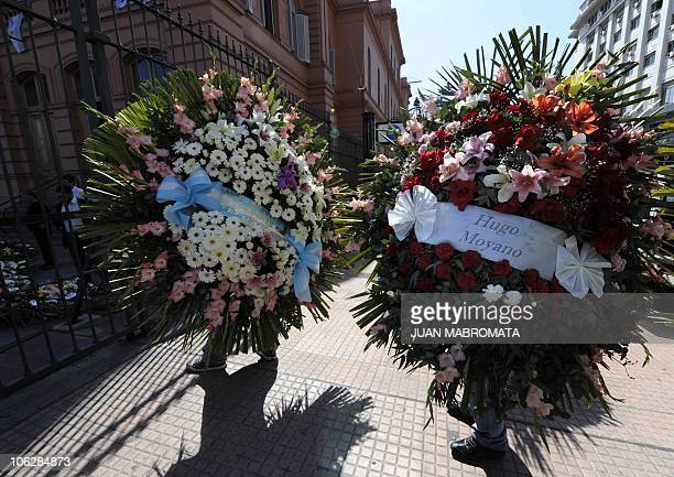 Workers carry wreaths of flowers into the Casa Rosada presidential palace in Buenos Aires for the wake of late former Argentine President Nestor...