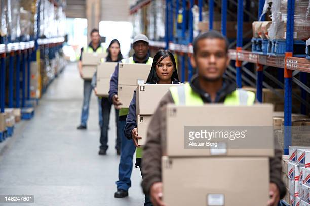 Workers carrying boxes in a warehouse
