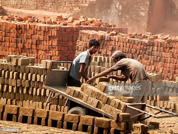 Workers carrying bricks at a brick factory in Bangladesh
