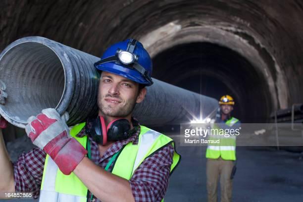 Arbeiter tragen lange pipe im tunnel