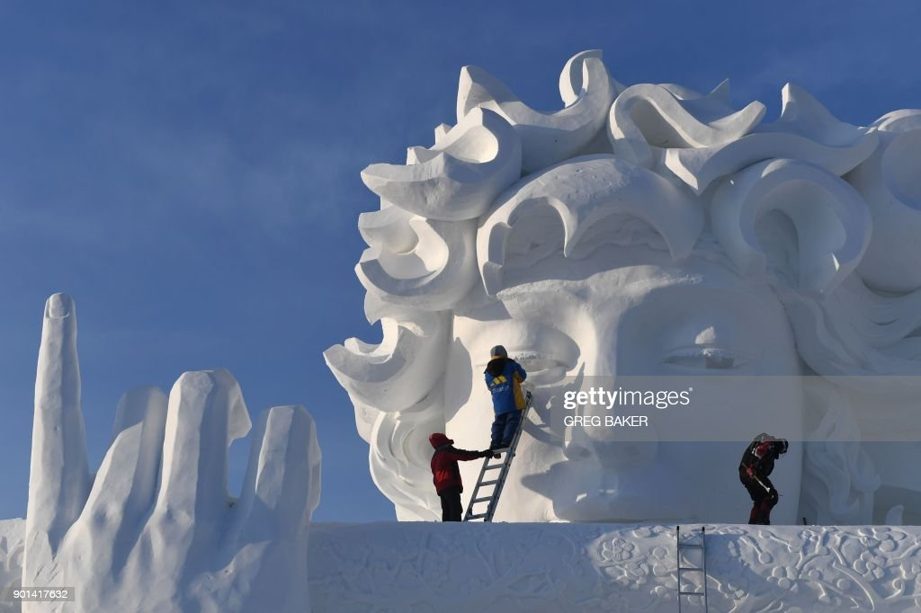 Workers carve a snow sculpture before the opening of the annual Harbin Ice and Snow Sculpture Festival in Harbin in China's northeast Heilongjiang province on January 5, 2018. The festival attracts hundreds of thousands of visitors annually. / AFP PHOTO / Greg Baker