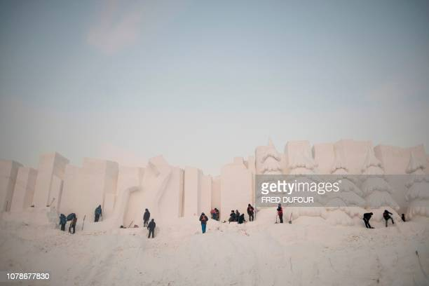 Workers carve snow sculptures during the annual Harbin Ice and Snow Festival in Harbin in China's northeast Heilongjiang province on January 7 2019
