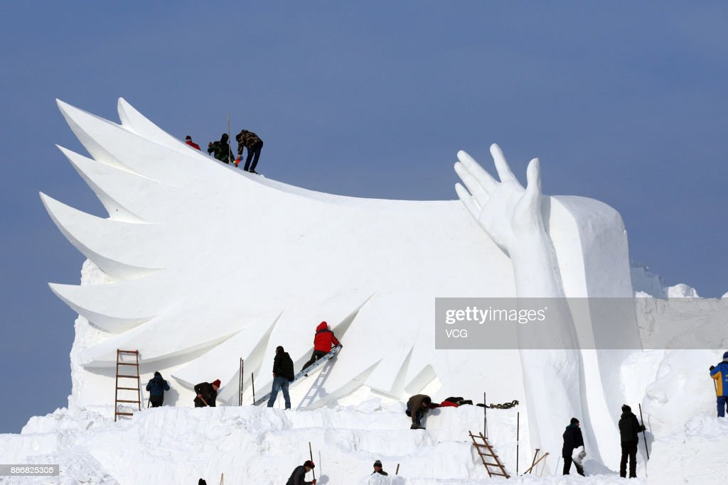 Workers carve the main sculpture of the 30th Harbin Sun Island International Snow Sculpture Art Exposition on December 6, 2017 in Harbin, Heilongjiang Province of China. The 30th Harbin Sun Island International Snow Sculpture Art Exposition is due to open on Dec 20. The 35-meter-tall main sculpture 'Snow song Winter Olympics' is designed to reach nearly 300 meters long with a big snow slide.