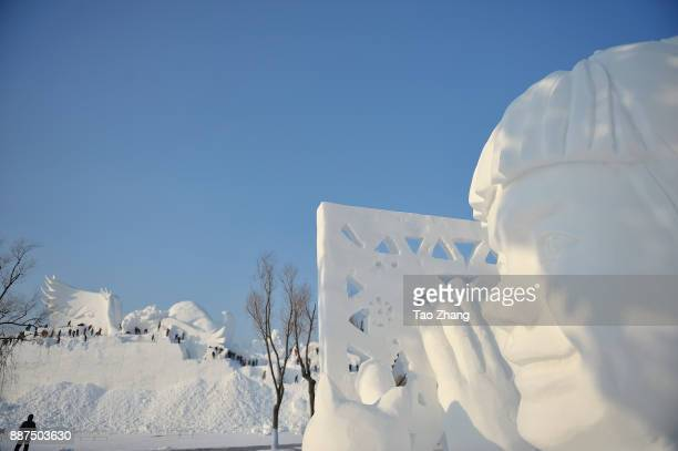 Workers carve the main sculpture 'Snow song Winter Olympics' for the 30th Harbin Sun Island international Snow Sculpture Art Exposition on December 7...