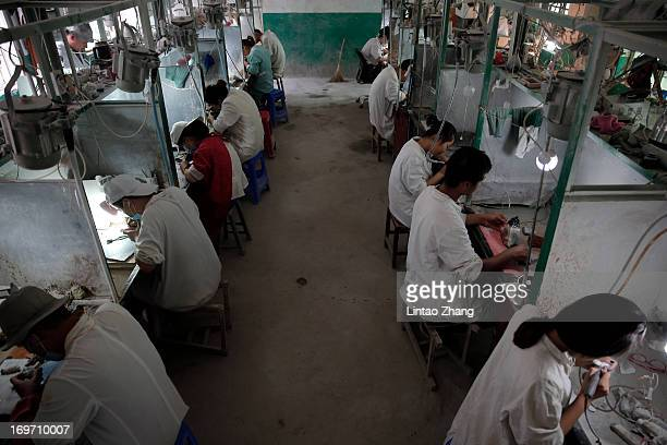 Workers carves on a jade at the Zhenping Jade Factory on May 27 in Zhenping county of the central province of Henan, China. Zhenping is one of the 14...