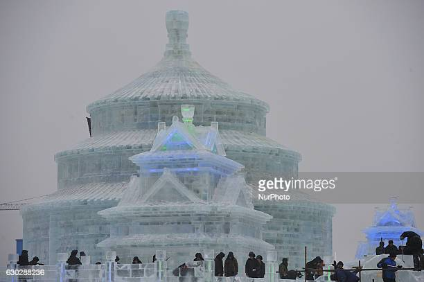 Workers carving ice sculpture at Ice and Snow World park in Harbin city of China on December 20 2016China's northernmost province of Heilongjiang...
