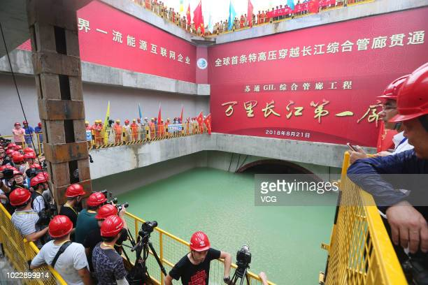 Workers celebrate the completion of the Nantong section of the world's first ever ultra-high voltage gas insulated underground power line on August...