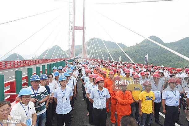 Workers celebrate the opening of express highway between Guiyang City and Qianxi County at a bridge connecting the two regions on July 16, 2016 in...
