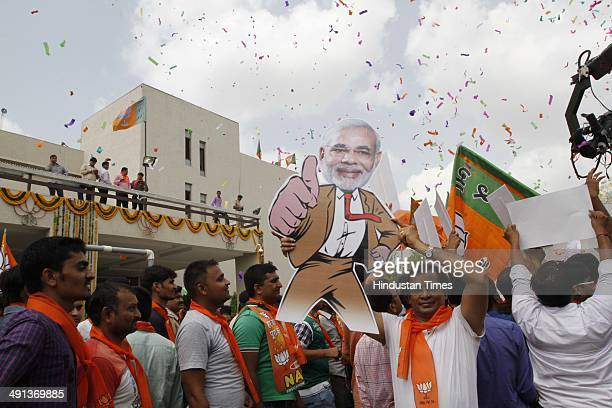 BJP workers celebrates with cutout of Gujarat Chief Minister and party prime ministerial candidate Narendra Modi as trends are showing a thumping...