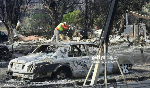 Workers check for gas lines amid the damaged homes from the Woolsey Fire on Filaree Heights Road in Malibu California on November 13 2018 At least 44...