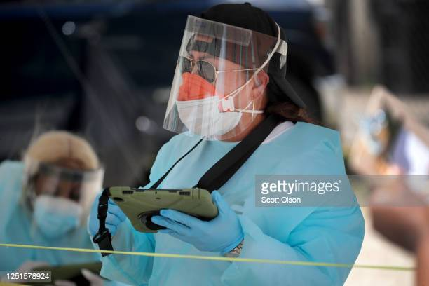 Workers check in residents at a mobile COVID-19 testing site set up on a vacant lot in the Austin neighborhood on June 23, 2020 in Chicago, Illinois....