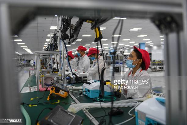 Workers check medical ventilators, which will be used by COVID-19 novel coronavirus patients, at a Vingroup production facility in Hanoi on August 3,...