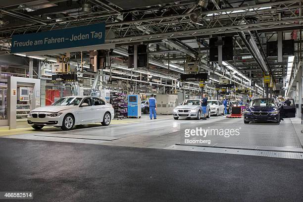 Workers check new BMW 3 series automobiles as they leave the final stage of the production line at the Bayerische Motoren Werke AG's plant in Munich...