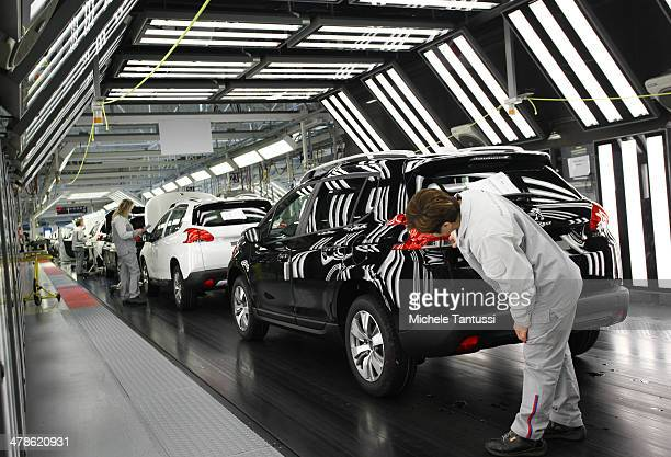 Workers check the body work of a Peugeot 2008 SUVs at the PSA Peugeot Citroen assembly plant on March 14 2014 in Mulhouse France Chinese automaker...