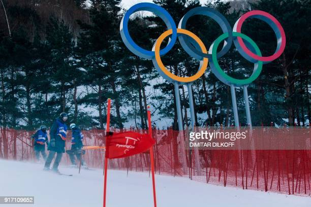 Workers check the course after the women's giant slalom was postponed due to high winds at the Jeongseon Alpine Center during the Pyeongchang 2018...